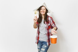 Young overjoyed beautiful woman in newspaper hat blinking and holding paint brush and paint bucket isolated on white background. Instruments, tools for renovation apartment room. Repair home concept.