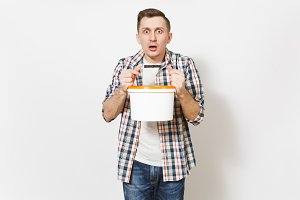 Young shocked handsome man in casual clothes holding empty paint bucket with copy space isolated on white background. Instruments, accessories for renovation apartment room. Repair home concept.
