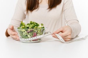 Close up cropped woman at table with green salad in glass bowl, tailor measuring tape isolated on white background. Proper nutrition, vegetarian food, healthy lifestyle, dieting concept. Copy space.