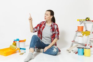 Woman pointing index finger aside on copy space, sit on floor with instruments for renovation apartment isolated on white background. Wallpaper accessories for gluing painting tools. Concept of repair