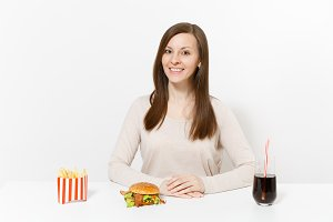 Beautiful smiling woman sitting at table with burger, french fries, cola in glass bottle isolated on white background. Proper nutrition or American classic fast food. Advertising area with copy space.