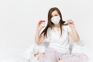 Young sick tired woman in mask on face sitting on bed, holding clinical thermometer with high fever temperature, bottle with white pills isolated on white background. Female feeling bad, time at home.