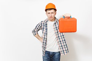 Young concerned man in protective construction helmet pointing case with instruments or toolbox on camera isolated on white background. Instruments for renovation apartment room. Repair home concept.