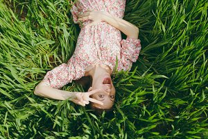 Young fun overjoyed beautiful woman in light patterned dress lying on grass showing victory sign resting in sunny weather in field on bright green background. Spring nature. Lifestyle concept.