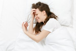 Top view of tired stressed crying young brunette woman lying in bed with white sheet, pillow, blanket. Shocked frustrated sad upset female lies on her side. Rest, relax, bad mood concept. Copy space.