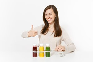 Young woman at table with green, red, yellow detox smoothies in bottles, measure tape isolated on white background. Proper nutrition, vegetarian drink, healthy lifestyle, dieting concept. Copy space.