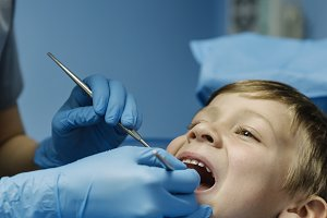 Dentists intervening a young patient