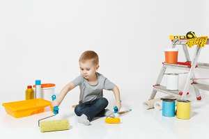 Little cute boy sitting on floor with instruments for renovation apartment room isolated on white background. Wallpaper, gluing accessories, painting tools. Repair home. Parenthood, childhood concept.