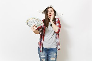 Young shocked beautiful woman in newspaper hat holding bundle of dollars, cash money and clinging to face isolated on white background. Instruments for renovation apartment room. Repair home concept.