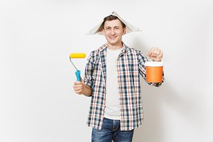 Smiling man in newspaper hat holding paint roller for wall painting and empty paint bucket with copy space isolated on white background. Instrument for renovation apartment room. Repair home concept.