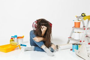 Confused annoyed tired shocked woman sitting on floor with instruments for renovation apartment isolated on white background. Wallpaper, accessories for gluing, painting tools. Concept of repair home.