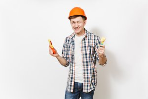 Young smiling handsome man in casual clothes and protective orange hardhat holding toy hammer and saw isolated on white background. Instruments for renovation apartment room. Repair home concept.