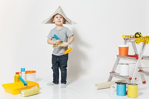 Little cute boy in newspaper hat with instruments for renovation apartment room isolated on white background. Wallpaper, gluing accessories, painting tools. Repair home. Parenthood, childhood concept.