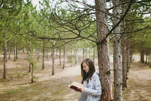 Young calm beautiful woman in casual clothes leaning on tree studying reading book in big city park or forest on green blurred background. Student learning, education. Lifestyle, leisure concept.