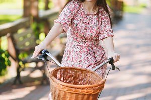 Portrait of trendy young woman in long pink floral dress riding on alley on vintage bike with basket for purchases, food or flowers outdoors, gorgeous female recreation time in spring or summer park.