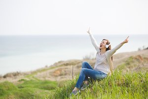 Young screaming fun pretty woman in casual clothes with headphones listening music sitting on grass spreading hands pointing index fingers up near water on green field background. Lifestyle concept.