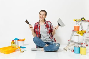 Woman in casual clothes sitting on floor with putty knife, instruments for renovation apartment room isolated on white background. Wallpaper accessories for gluing painting tools. Repair home concept.