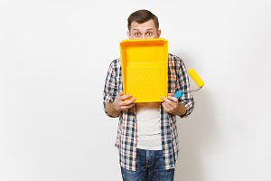 Young shocked handsome man holding paint roller for wall painting and covering face with paint tray isolated on white background. Instruments, tools for renovation apartment room. Repair home concept.