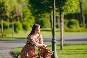 Portrait of trendy young woman in long pink floral dress stop to riding on vintage bike with basket for purchases, food or flowers outdoors, gorgeous female recreation time in spring or summer park.