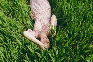 Young smiling woman in light patterned dress lying on grass keeping hands near head looking up resting in sunny weather in field on bright green background. Spring nature. Lifestyle, leisure concept.