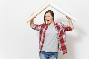 Young overjoyed woman in casual clothes holding wallpaper rolls above head in form of roof isolated on white background. Instruments, accessories for renovation apartment room. Repair home concept.