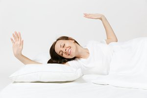Calm young woman lying in bed with white sheet, pillow, blanket on white background. Smiling beauty female stretching out in bed in room. Rest, relax, good mood concept. Copy space for advertisement.