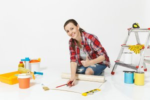 Woman sitting with wallpaper rolls, stationery knife, pencil, instruments for renovation apartment isolated on white background. Accessories for gluing, painting tools. Repair home concept. Copy space