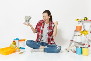 Woman holds bundle of cash money, supermarket grocery push cart for shopping. Instruments for renovation apartment isolated on white background. Wallpaper accessories for gluing. Repair home concept.