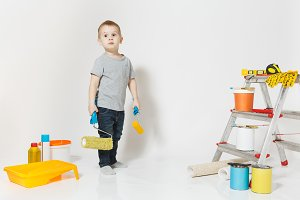 Little cute boy standing with instruments for renovation apartment room isolated on white background. Wallpaper, gluing accessories, painting tools. Son repairing home. Parenthood, childhood concept.