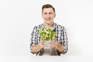 Young happy fun man sitting and throwing up salad from glass bowl isolated on white background. Proper nutrition, vegetarian food, healthy lifestyle, dieting concept. Advertising area to copy space