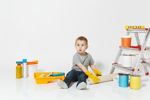 Little cute boy in yellow gloves with instruments for renovation apartment room isolated on white background. Wallpaper, gluing accessories, painting tools. Repair home. Parenthood, childhood concept.