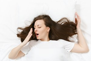 Top view of head of happy brunette young woman lying in bed with white sheet, pillow, blanket. Yawning pretty female spending time in room. Rest, relax, good mood concept. Copy space for advertisement