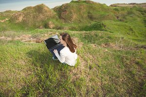 Young business woman or student sitting on grass using laptop with blank empty screen monitor in field spreading hands working outdoors on green background. Mobile Office. Lifestyle concept. Back view