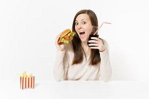 Happy fun young woman sitting at table with burger, french fries, cola in glass bottle isolated on white background. Proper nutrition or American classic fast food. Advertising area with copy space.