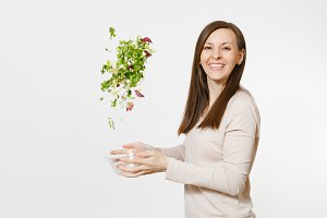 Young happy fun woman standing and throwing up salad from glass bowl isolated on white background. Proper nutrition, vegetarian food, healthy lifestyle, dieting concept. Advertising area to copy space