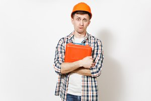 Young concerned handsome man in protective orange hardhat holding case with instruments or toolbox isolated on white background. Instruments, tools for renovation apartment room. Repair home concept.