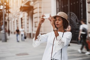 Black girl in hat with cellphone