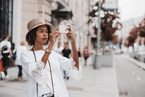 Black girl photographing on street