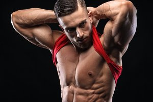 Cute young sports man in red t-shirt shows relief abdominal muscles