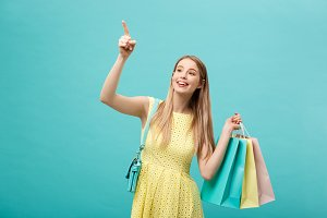 Shopping Concept: Portrait of an excited beautiful girl wearing yellow dress holding shopping bags isolated over blue background