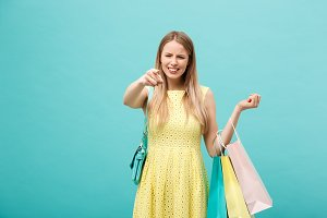 Shoping and Sale Concept: beautiful unhappy young woman in yellow elegant dress with shopping bag.
