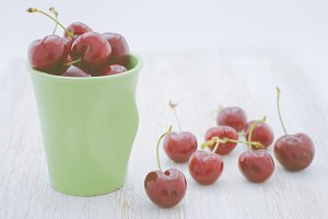 Cherries in a bowl and white wooden