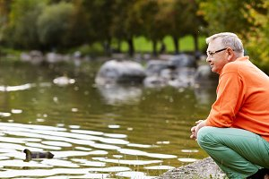 Mature man crouching near pond
