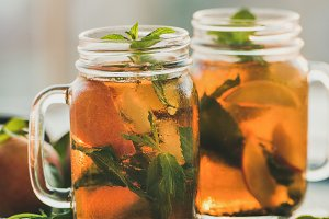 Summer refreshing cold peach ice tea on tray, vertical composition