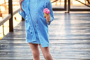 Beautiful fashionable little lady girl resting on bridge port. Child looks away,smiles,holds ice cream. Fashion young kid, elegant summer clothes in striped,blue costume dress in marine style,cruise.