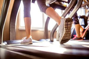 Detail of legs of woman running on treadmills gym