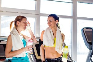 Two women in gym with water bottles and towels