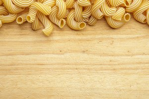dried pasta on wooden background.