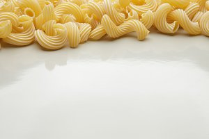 Group of macaroni pasta on gray background