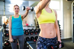 Two fit women in gym working out with weights